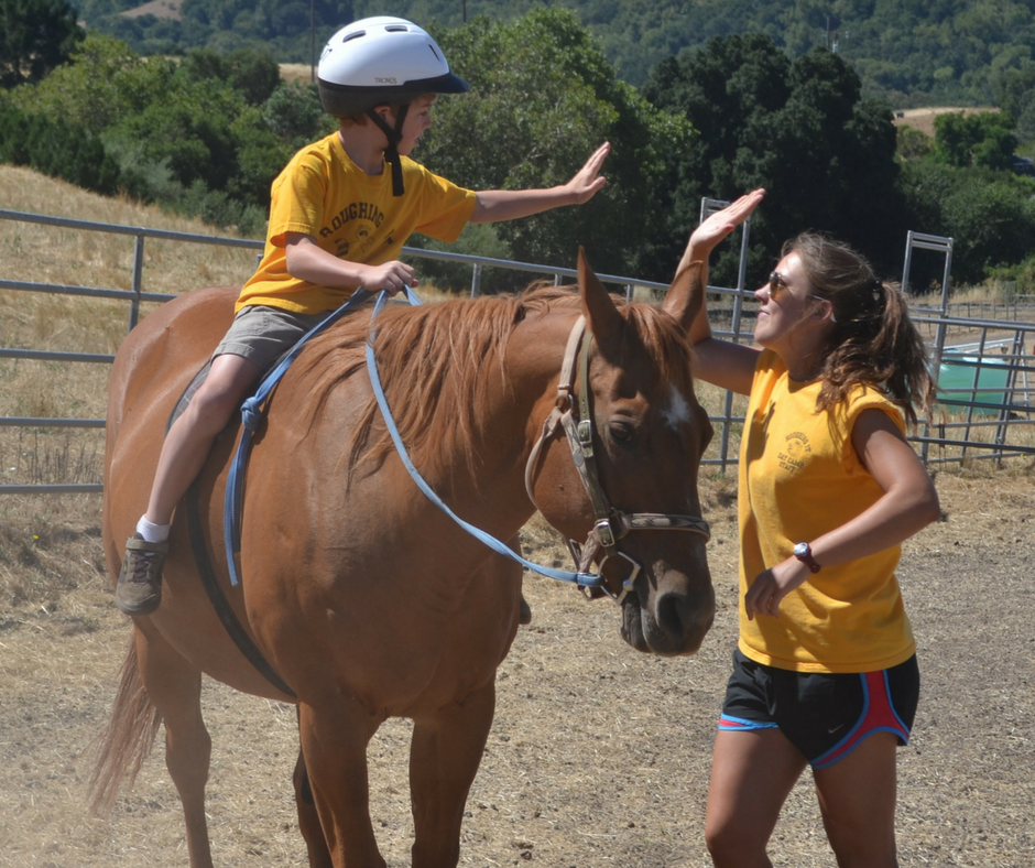 Horse counselor giving their camper a high five