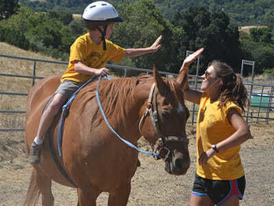 Young Camper and Counselor High Five at the Ride Site