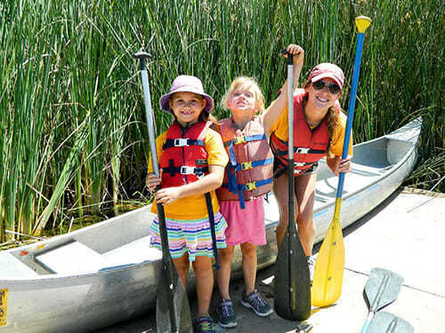 Campers posing with the counselor and canoe