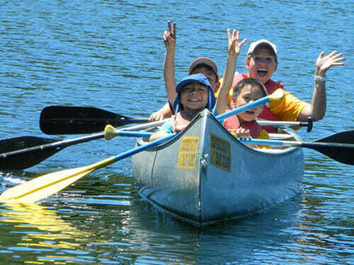Campers waving to the camera from their canoe