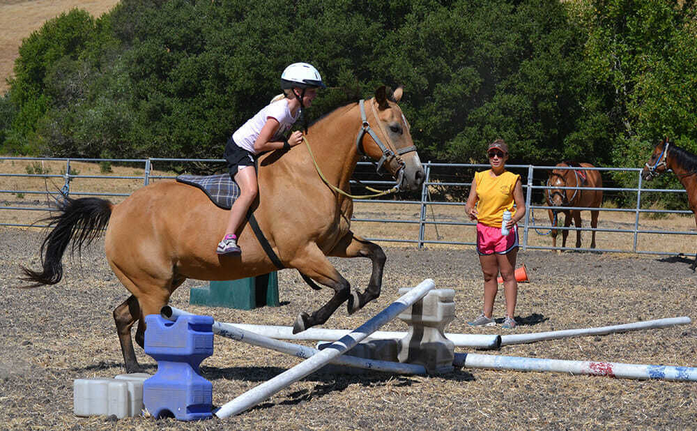 Teen Camper Performs Jump on Horse