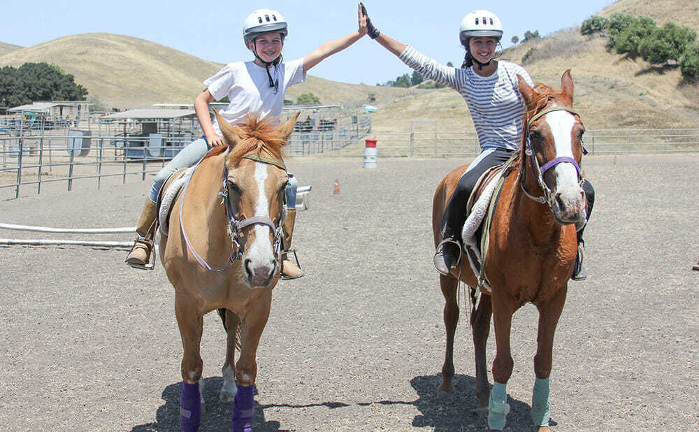 Two Camp Friends High-Five while Sitting on their Horses