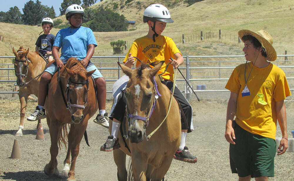 Teen Boy Campers Ride Horses in a Line Around the Ring