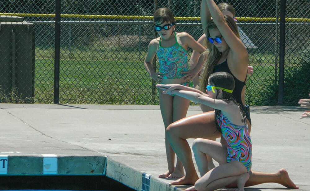 Swimming Counselor Leads Teen Campers in Diving Lesson