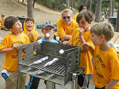 Young Boy Campers Roast Marshmallows over the Grill
