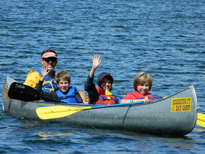 Teen Campers Wave from a Canoe