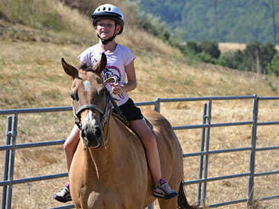 Girl Camper Takes Horse Around Ring During Riding