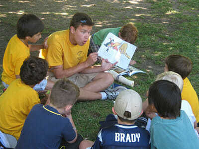 Young Boy Campers Hear a Story from a Picture Book