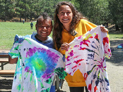 Camper and Counselor Smile While Holding Freshly Tie-Dyed Shirts