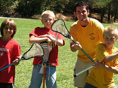 Young Boy Campers Hold Lacrosse Sticks at Sports