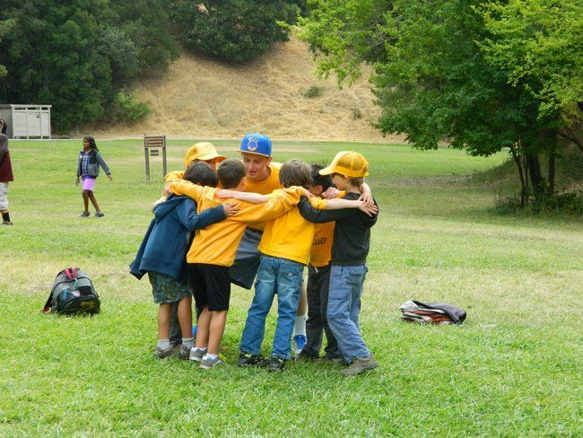 young boy campers huddle with team at roughing it day camp at the lafayette reservoir with counselor