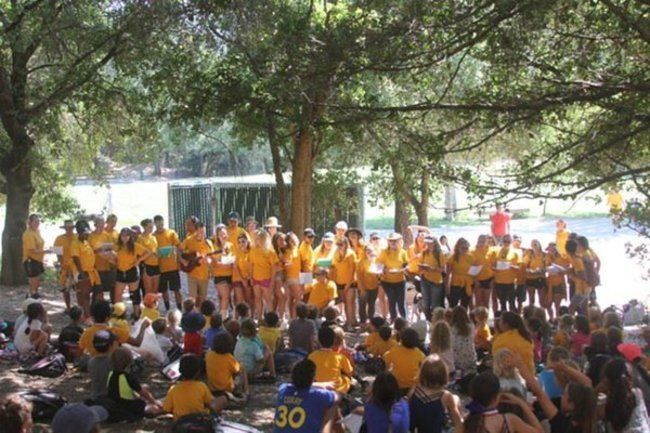 Counselors sing camp song to campers at closign circle at lafayette reservoir