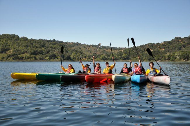 teen campers and counselros at Roughing It day camp smiling in kayaks together at the lafayette reservoir