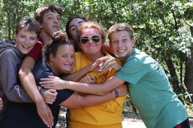 teen campers hugging counselor at roughing it day camp at the lafayette reservoir.
