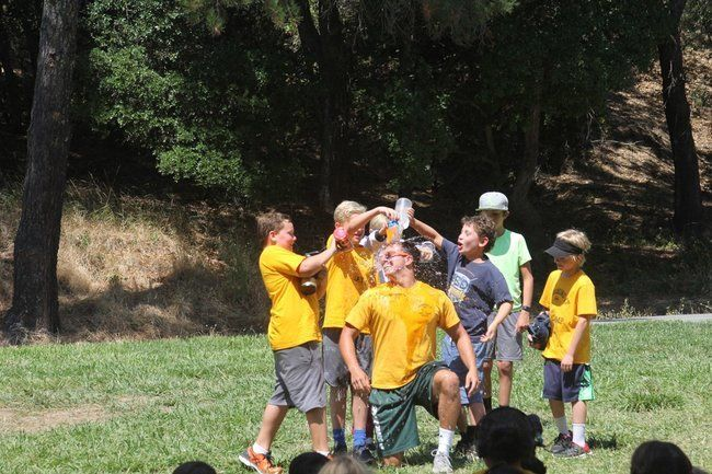boy campers pouring water on their counselor at roughing it day camp for skit at the lafayette reservoir