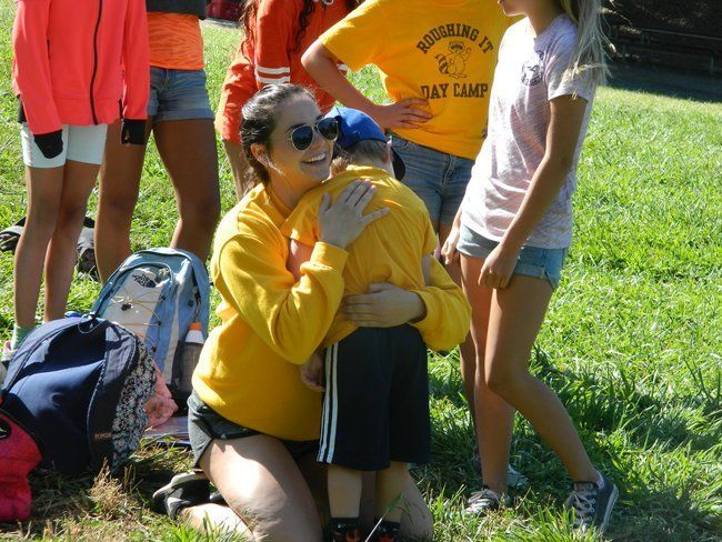 counselor at roughing it day camp hugging young camper at lafayette reservoir