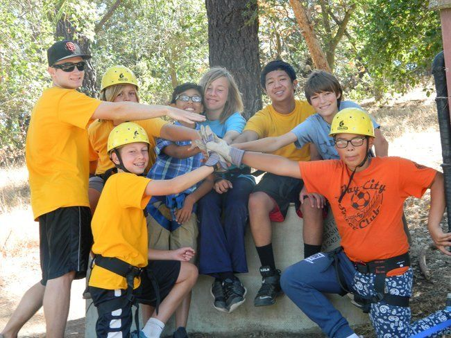 campers and counselor at roughing it day camp in teamwork huddle before beginning rock climbing